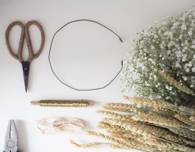 table avec ciseaux fil de fer paille fleurs pour faire une couronne de fleurs
