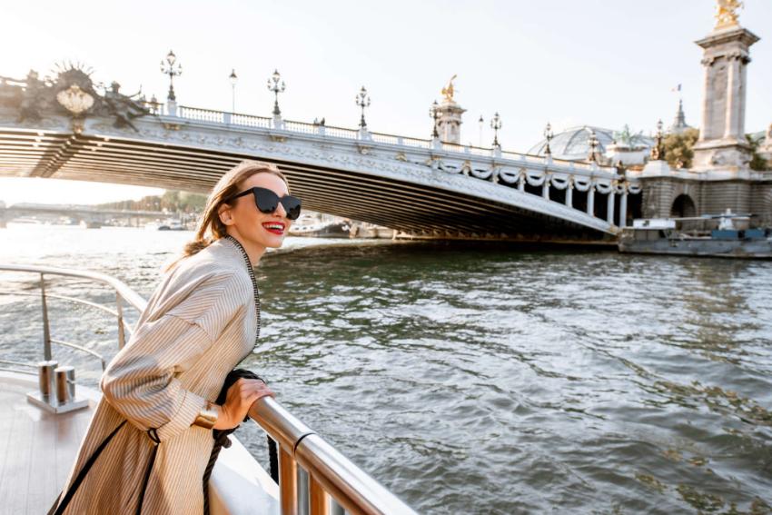 fille en croissiere sur un bateau une peniche a paris sur la seine avec un pont un monument en arriere plan